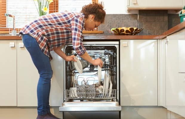 woman placing dishes in a dishwasher
